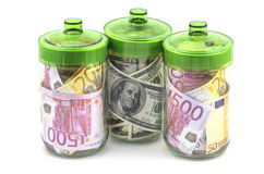 Money in banks. Bills euro and dollars in glass banks on white background Stock Images