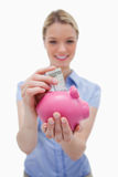 Money being put into piggy bank by woman Stock Images