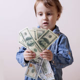 Money is the best motivation. A child holding dollars banknotes. Stock Images