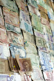 Money bills from all around the world. A lot of money bills from differents countries attached to a wall. internacional economy mataphore Stock Photo