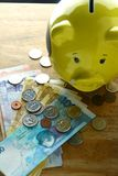 Money Bills and a coin bank on a table Royalty Free Stock Photos