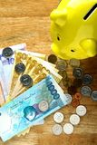 Money Bills and a coin bank on a table Royalty Free Stock Images