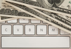 Money bills on computer keyboard with spacebar Royalty Free Stock Photography