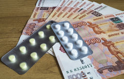 Money bills with medical tablet. Money bills are with medical tablet to rest upon wooden table Royalty Free Stock Photos