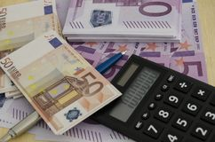 Many 500 and 50 euro bills with a pen and a calculator with a mi. 500 and 50 money bills next to a calculator showing a million indicating the success of having Stock Images
