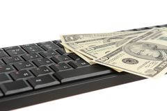 Money on black keyboard isolated on white Royalty Free Stock Photography
