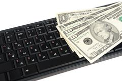 Money on black keyboard isolated on white Stock Photo