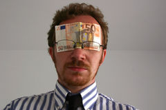 Money blinds. Man with €50 note/bill covering his eyes depicting money blinds Stock Photography