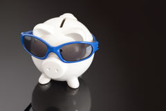Money Blues. Concept shot of a piggy bank with sunglasses looking like its taking a holiday Stock Photos
