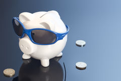 Money Blues. Concept shot of a piggy bank with sunglasses looking like its taking a holiday Royalty Free Stock Photo