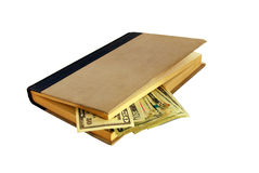 Money in book. Money in the form of many large bills hidden in an old book Stock Image