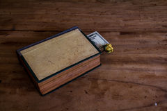 The money is in the book on the old wooden floor.still life Stock Photography