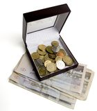 Money box 1. Some coins in a box on top of the bills. Contains clipping path isolation Royalty Free Stock Image