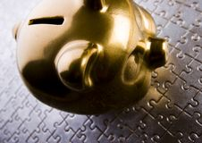 Money box. Piggy bank on jigsaws & on the silver background Stock Photography