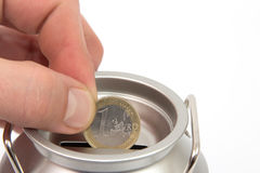 Money box with coin. Money box and and a coin between fingers with a white background Stock Photography