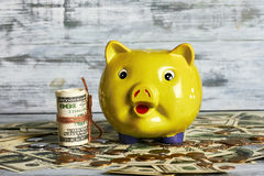 Money box and dollars. Coins on wooden surface. Capital for purchase Stock Photos