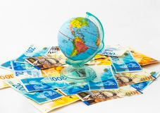 A money box made in the form of a globe, the planet Earth with a money slot at the top stands on a stack of Israeli banknotes of d. Ifferent value on a white stock images