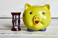 Money box and sandglass. Goal is close Royalty Free Stock Photo