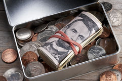 Money Box Savings. A tin box with a roll of American money and coins stock images