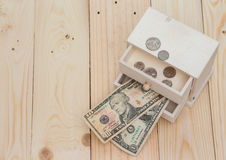 Money in the box on wooden background. Money in the box on oak wood background Royalty Free Stock Images