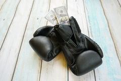 Money with boxing gloves. On wooden background Royalty Free Stock Image