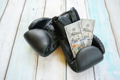 Money with boxing gloves. On wooden background Royalty Free Stock Photography