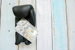 Money with boxing gloves. On wooden background Royalty Free Stock Photos