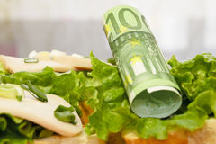 Money at breakfast. One hundred euro on a sandwich Royalty Free Stock Photos