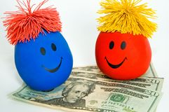 Money Brings Lots of Smiles!. Two colorful toy smiley faces sit on top of several twenty dollar bills (US) on a white background. Useful for any number of stock photo