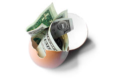 Money in broken egg. Overhead view of dollar banknotes in broken egg with white background royalty free stock images