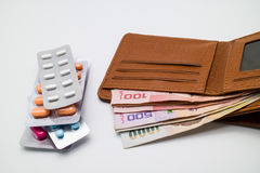 Money in brown wallet with blisters of pills. Royalty Free Stock Photography