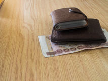 Money in a brown wallet Stock Photo