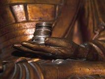 Money in Buddhas Hand Stock Photo