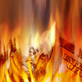 Money Burning in Flames. Burning American money with Benjamin Franklins face appearing on fire on a one hundred dollar bill Royalty Free Stock Photography