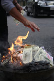 Money burning. US Dollars and Vietnam Dongs are burned up on the Royalty Free Stock Photography