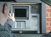 Money business. Withdrawing cash from money machine in a parking lot stock photo