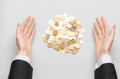 Money and Business theme: hands in a black suit indicates a pile of gold coins on a white table in the studio Royalty Free Stock Photo
