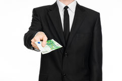 Money and business theme: a man in a black suit holding a banknote 100 euro isolated on a white background in studio Stock Photos