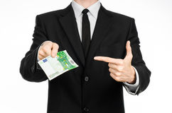Money and business theme: a man in a black suit holding a bill of 100 euros and shows a hand gesture on an isolated white backgrou Royalty Free Stock Photos