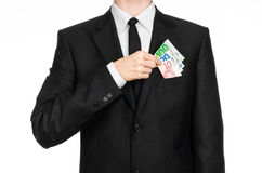 Money and business theme: a man in a black suit is holding euro money isolated on white background in studio Stock Photos