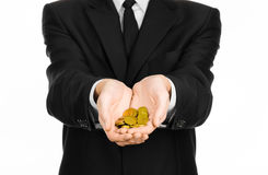 Money and business theme: a man in a black suit holding a pile of gold coins in the studio on a white background isolated Stock Image
