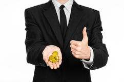 Money and business theme: a man in a black suit holding a pile of gold coins in the studio on a white background isolated Royalty Free Stock Photo
