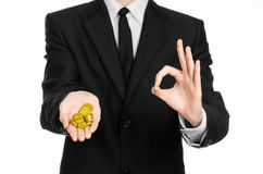 Money and business theme: a man in a black suit holding a pile of gold coins in the studio on a white background isolated. Money and business theme: a man in a Royalty Free Stock Image