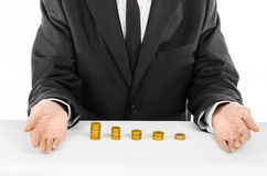 Money and business theme: a man in a black suit indicates the chart bars of gold coins on a white table in the studio on a white b Stock Images