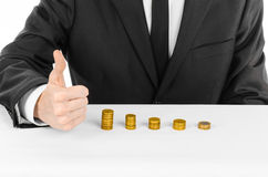 Money and business theme: a man in a black suit indicates the chart bars of gold coins on a white table in the studio on a white b Stock Image