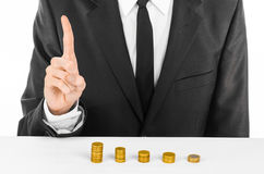 Money and business theme: a man in a black suit indicates the chart bars of gold coins on a white table in the studio on a white b Royalty Free Stock Photos