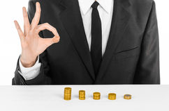 Money and business theme: a man in a black suit indicates the chart bars of gold coins on a white table in the studio on a white b Royalty Free Stock Photography