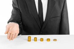 Money and business theme: a man in a black suit indicates the chart bars of gold coins on a white table in the studio on a white b. Ackground Stock Photo