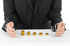 Money and business theme: a man in a black suit indicates the chart bars of gold coins on a white table in the studio on a white b Royalty Free Stock Images