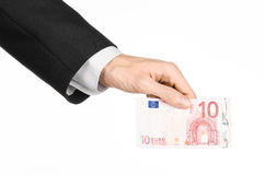 Money and business topic: hand in a black suit holding a banknote 10 euro isolated on a white background in studio Royalty Free Stock Photo